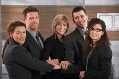 Business team. Team portrait of happy businesspeople standing in office with joined hands, smiling Stock Images