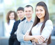 Business team. A business team with pretty leader in front looking at camera and smiling Royalty Free Stock Photography