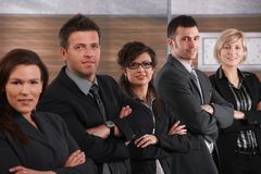 Business team. Portrait of business team standing in a row with arms crossed, smiling royalty free stock photos