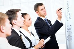 Business team. Young businessman presenting his ideas on whiteboard to colleagues Royalty Free Stock Photo
