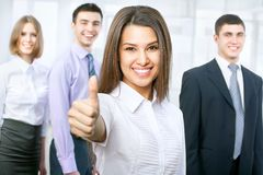 Business team. Portrait of female leader showing thumb up with cheerful team in background Royalty Free Stock Photography