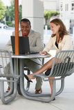 Business Team. An attractive man and woman business team busy working outside Stock Photography