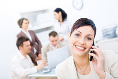 Business team. Businesswoman sitting in front, calling on phone, looking at camera, smiling. Four business colleagues working on laptop computer in background stock photo
