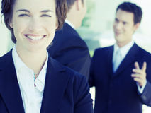 Business team. One business woman staring at camera while two businessmen talk in background Royalty Free Stock Images