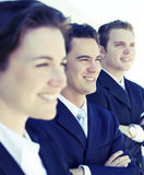 Business team. Three business people standing in a row with arms folded looking in the same direction Stock Photography