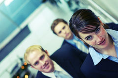Business team. Three business people looking towards camera and walking up stairs Royalty Free Stock Image