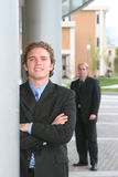 Business team. Two businessmen standing in full suits with folded arms Stock Photo
