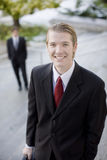 Business team. Two businessmen standing on steps with hands in pockets holding briefcase smiling Royalty Free Stock Photo