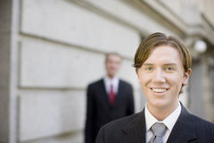 Business team. Two businessmen standing in suits looking at camera wearing suits Royalty Free Stock Photo