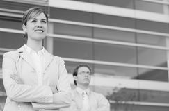 Business team. Businesswoman and businessman standing side by side with arms folded looking forward stock images