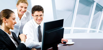 Business team. Team of three business people looking at monitor of computer in the office Royalty Free Stock Image