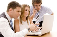 Business Team. A business team of three works on a laptop computer Royalty Free Stock Photos