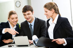 Business team. Image of business team sitting at the table and discussing a computer work
