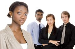 Business Team. A young businesswoman (in focus) stands in front of her diverse business team (off focus Stock Image