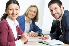 Business team. Three professionals looking at camera during briefing royalty free stock images