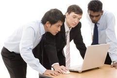 Business Team 9. Three businessmen confer around a laptop computer Royalty Free Stock Photos