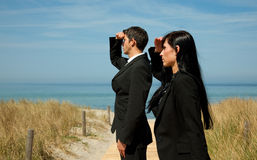Business team. Formal man and woman as investmentteam standing on the sunny beach Stock Photos