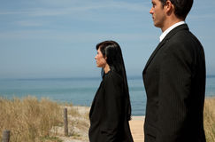 Business team. Formal man and woman as investmentteam standing on the sunny beach Stock Images