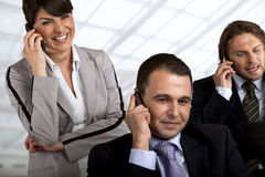 Business team in action. Three businesspeople talking on their cellular phones Stock Photos