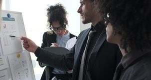 Business team analyzing reports on whiteboard at office. Business team analyzing and discussing financial reports on whiteboard at office meeting stock footage