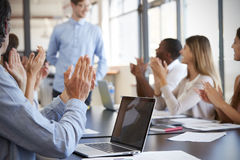 Business team applauding colleague at a meeting Stock Image