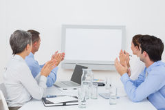 Business team applauding and looking at white screen Royalty Free Stock Image