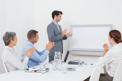 Business team applauding and looking at white screen Stock Photos