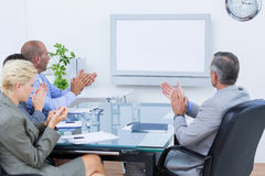 Business team applauding and looking at white screen Royalty Free Stock Images