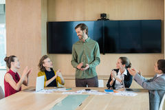 Business team applauding their colleague in conference room. At office Royalty Free Stock Images