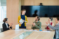 Business team applauding their colleague in conference room. At office Stock Photography