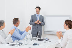 Business team applauding their colleague Royalty Free Stock Image
