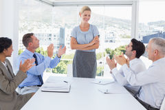 Business team applauding their colleague Stock Images