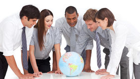 Business team around a terrestrial globe. A meeting of business team around a terrestrial globe against a white background stock photography