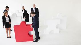 Business team and big puzzle. Business team assembling big puzzle on white background stock video footage