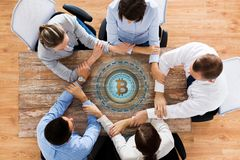 Business team with bitcoin hologram holding hands Stock Photography