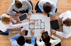 Business team with blueprint and gadgets Stock Images