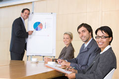 Business team in boardroom. Business man giving presentation to business team in boardroom Royalty Free Stock Photo