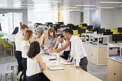 Business team brainstorm in open plan office, elevated view stock photo