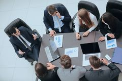 Business team discussing in office financial issues. Business team at a briefing discussing financial charts royalty free stock image