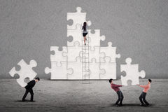 Business teamwork building puzzle. Business team building puzzles together on grey background Royalty Free Stock Photos