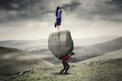 Business team with burden on the hill. Portrait of women entrepreneur standing on the stone and looking through binocular while her partner lifting boulder on Royalty Free Stock Photos