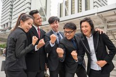 Business team celebrate success with arms raised Stock Photo