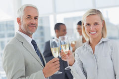 Business team celebrating with champagne and looking at camera Royalty Free Stock Image
