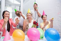 Business team celebrating with champagne and party horns royalty free stock images