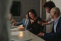 Business team celebrating female colleague`s birthday. With cake in office. Birthday celebration of a female associate during a staff meeting Stock Photos
