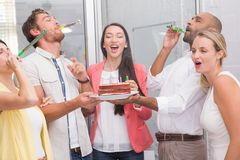Business team celebrating with party horns royalty free stock image