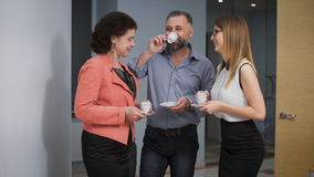 Business Team Coffee Break Relax Concept. Business people colleagues communicate in an informal setting, laughing. Taken in an office corridor stock footage