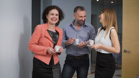 Business Team Coffee Break Relax Concept. Business people colleagues communicate in an informal setting, laughing. Taken in an office corridor stock video