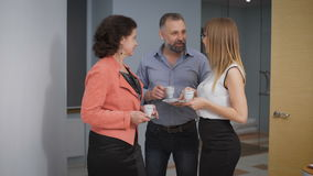 Business Team Coffee Break Relax Concept. Business people colleagues communicate in an informal setting, laughing. Taken in an office corridor stock video footage