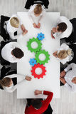 Business team with cogs. Business team sitting around the table with cogs, teamwork concept Stock Images